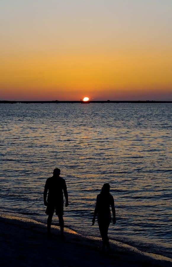 Gente en la playa en la puesta del sol foto de archivo