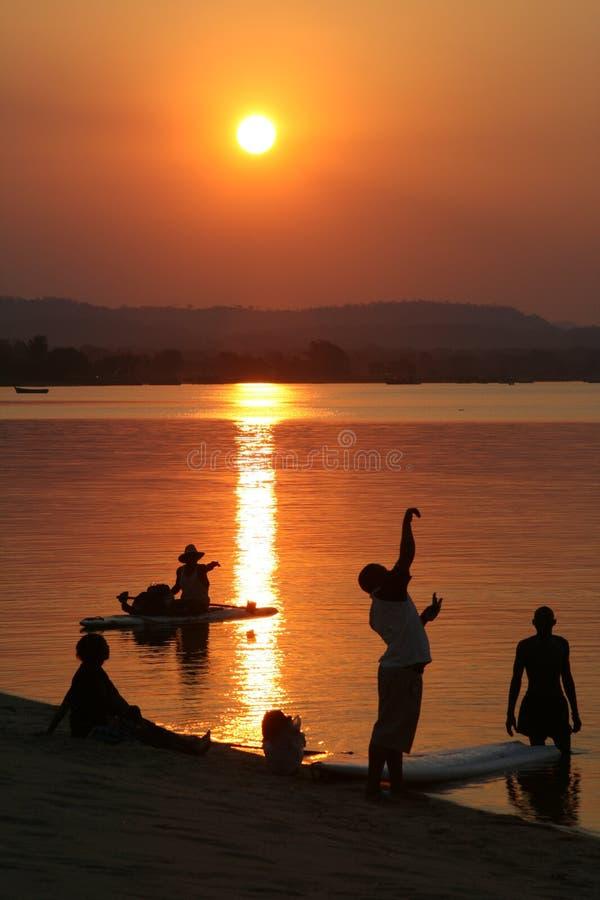 Gente en la playa en la puesta del sol imagenes de archivo