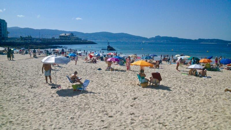 Gente en la playa en Sanxenxo España con Madama de Silgar en el fondo imagen de archivo