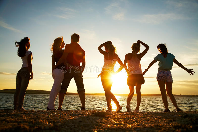 Gente en la puesta del sol de la playa imagen de archivo