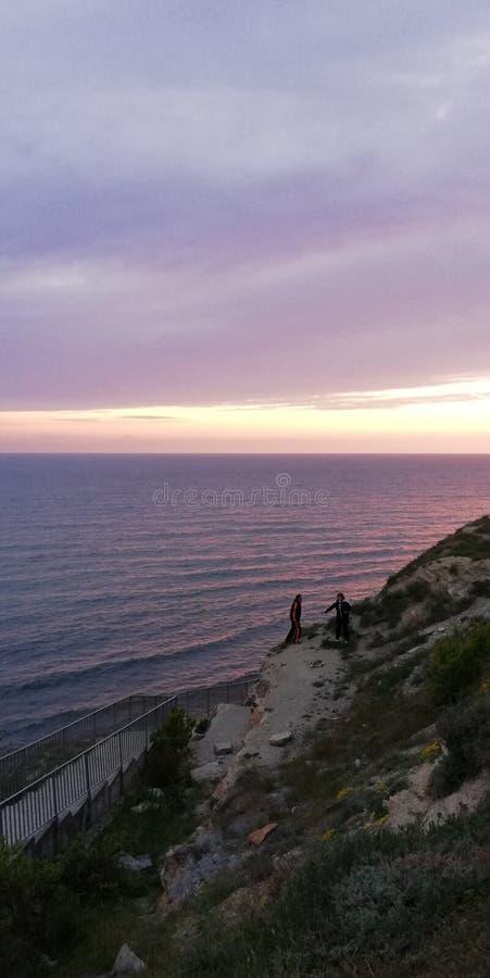 Gente en la roca contra el paisaje del mar de la puesta del sol El mar y el cielo se pintan en rosa y colores p?rpuras Fondo esc? foto de archivo