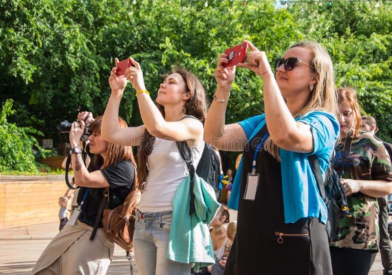 Gente en la terraza del verano tomar las fotos foto de archivo