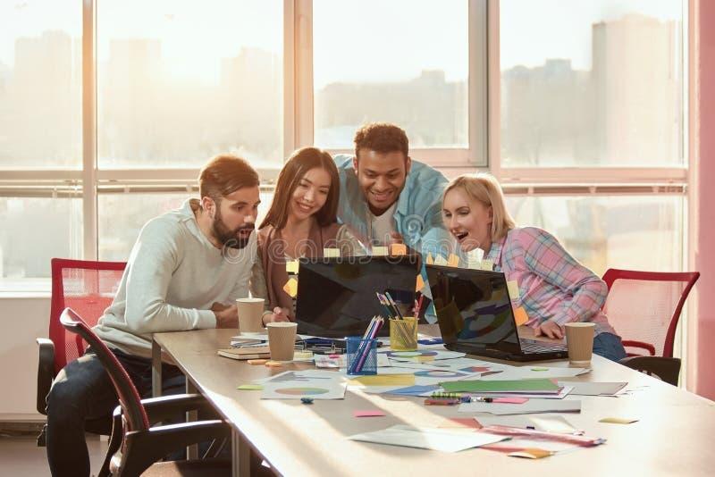 Gente en oficina que mira los vídeos divertidos en el ordenador portátil fotos de archivo