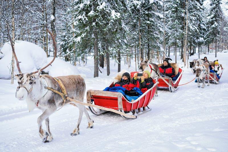 Gente en safari de la caravana del trineo del reno en el bosque Rovani del invierno imagenes de archivo