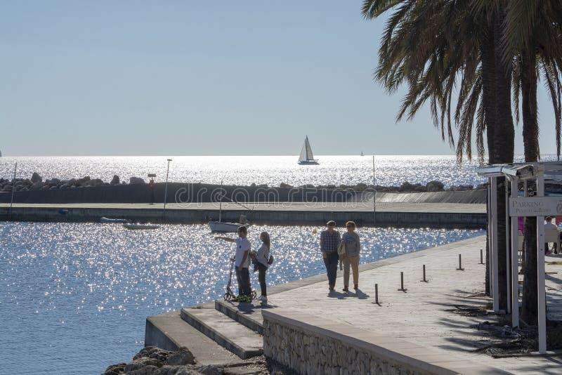 Gente en siluetas en el embarcadero por el mar chispeante brillante imagen de archivo