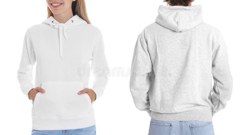 Gente en suéteres en blanco de la sudadera con capucha en el fondo blanco, primer foto de archivo