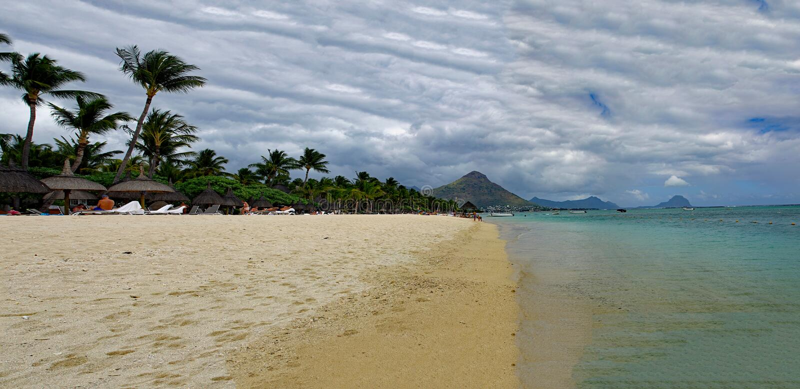 Gente en un día soleado caminando en la playa pública de Flic en Flac con árboles tropicales en el borde del Océano Índico, M fotografía de archivo libre de regalías