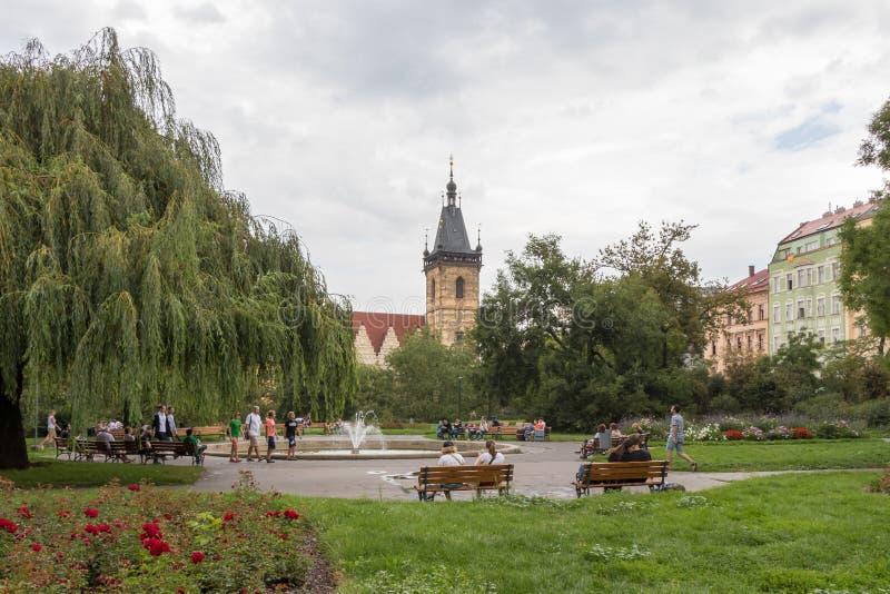 Gente en un parque y nuevo ayuntamiento de la ciudad en Praga imagenes de archivo