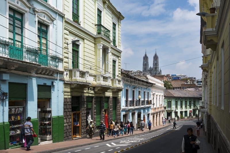 Gente en una calle en el centro histórico de la ciudad de Quito, en Ecuador, con la basílica del voto nacional en el backgroun foto de archivo