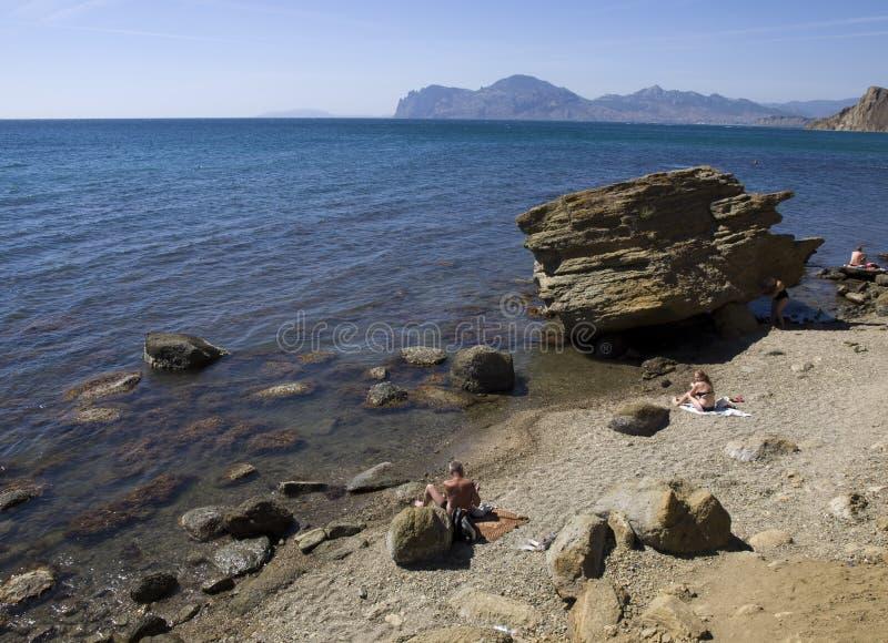 Gente en una playa salvaje fotos de archivo
