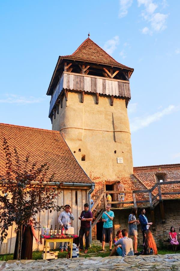 Gente en una reunión en la iglesia fortificada de Alma Vii, región de Transilvania, Rumania del brunch y de la degustación de vin imagenes de archivo