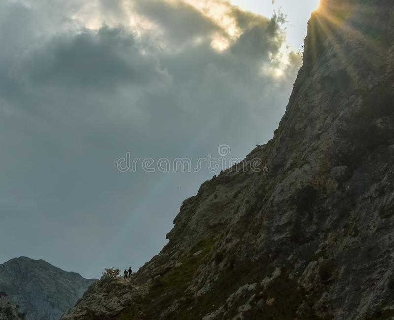 Gente en una ruta que emigra con los picos en la parte inferior en la puesta del sol, Asturias imagen de archivo