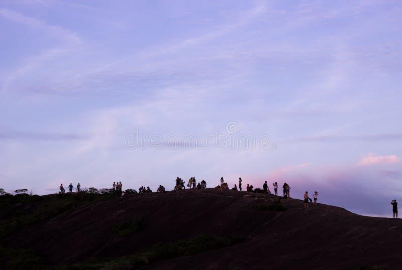Gente encima de la colina desde arriba de la silueta que causa de piedra foto de archivo