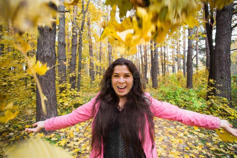 Gente, estación y concepto de la emoción - la mujer sonriente bonita joven se divierte en el parque del otoño fotografía de archivo