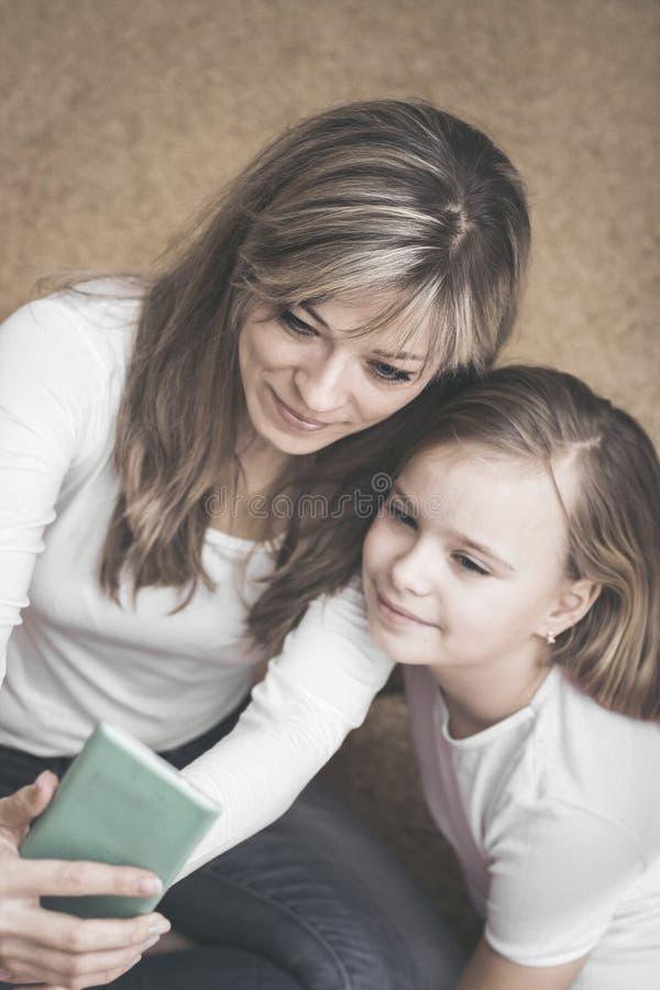 Gente, familia y concepto de la tecnología - muchacha y madre felices con smartphone en casa fotos de archivo libres de regalías