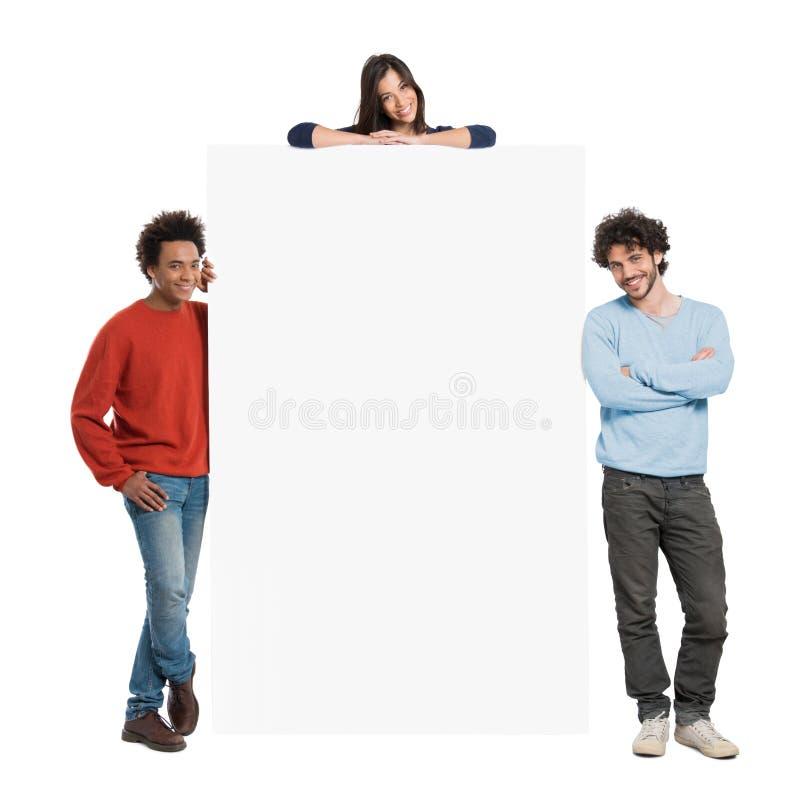 Gente felice che mostra tabellone per le affissioni immagine stock