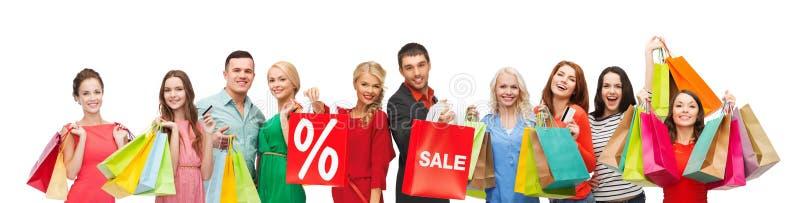 Gente feliz con la muestra de la venta en los panieres fotos de archivo libres de regalías