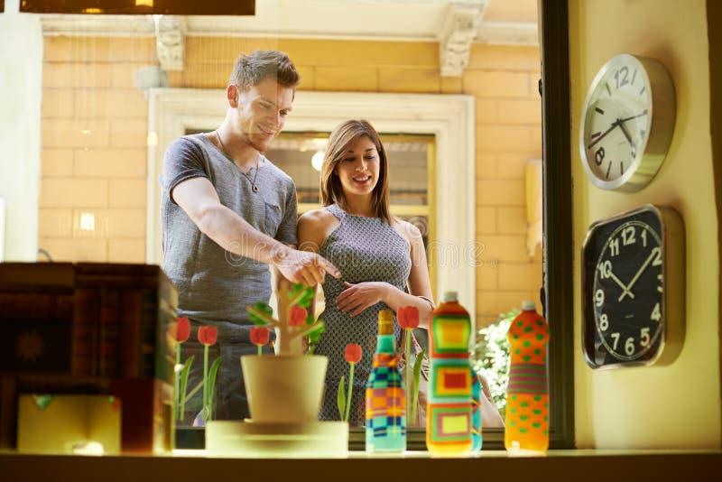 Gente feliz con los pares en la tienda y las compras de la ventana foto de archivo