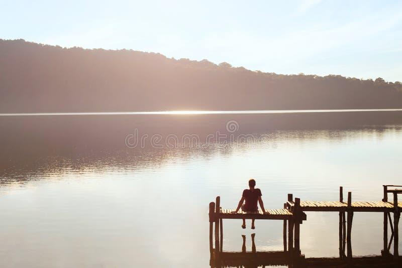 Gente feliz, daydreamer, hombre que disfruta de la hermosa vista del lago, inspiración imagenes de archivo