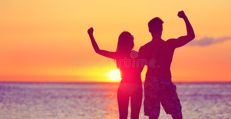 Gente feliz de la aptitud en la playa en doblar de la puesta del sol fotos de archivo