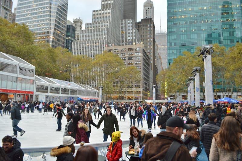 Gente feliz de la pista de Bryant Park Celebration Ice Skating del día de fiesta de la Navidad de New York City que goza divirtié imágenes de archivo libres de regalías