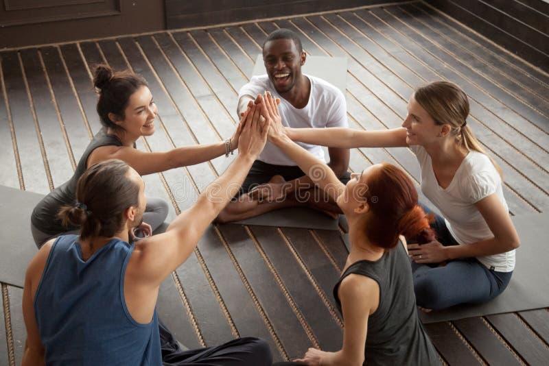 Gente feliz diversa que da el alto cinco en el entrenamiento del grupo fotografía de archivo