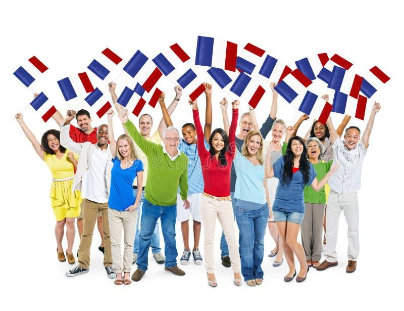 Gente feliz diversa que sostiene la bandera de Francia imagen de archivo