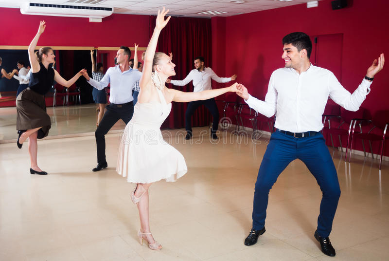 Gente feliz que baila el salto lindy en pares foto de archivo