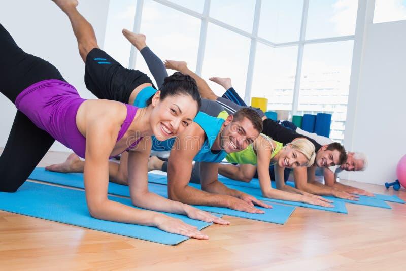 Gente feliz que ejercita en las esteras de la aptitud en el gimnasio imagen de archivo libre de regalías