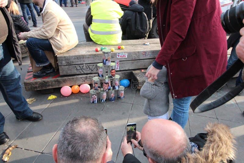 Gente fotografiando una pila de latas con las caras de políticos franceses como Emmanuel Macron imagen de archivo