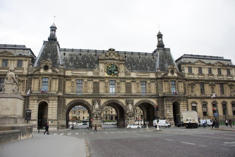 Gente francesa que conduce y biking con los viajeros que caminan y el camino del tráfico en el frente de Musee du Louvre imagen de archivo libre de regalías