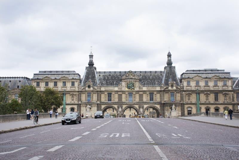 Gente francesa que conduce y biking con los viajeros que caminan y el camino del tráfico en el frente de Musee du Louvre imagen de archivo