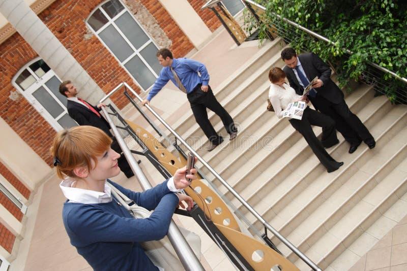 Gente fuera del edificio de oficinas foto de archivo
