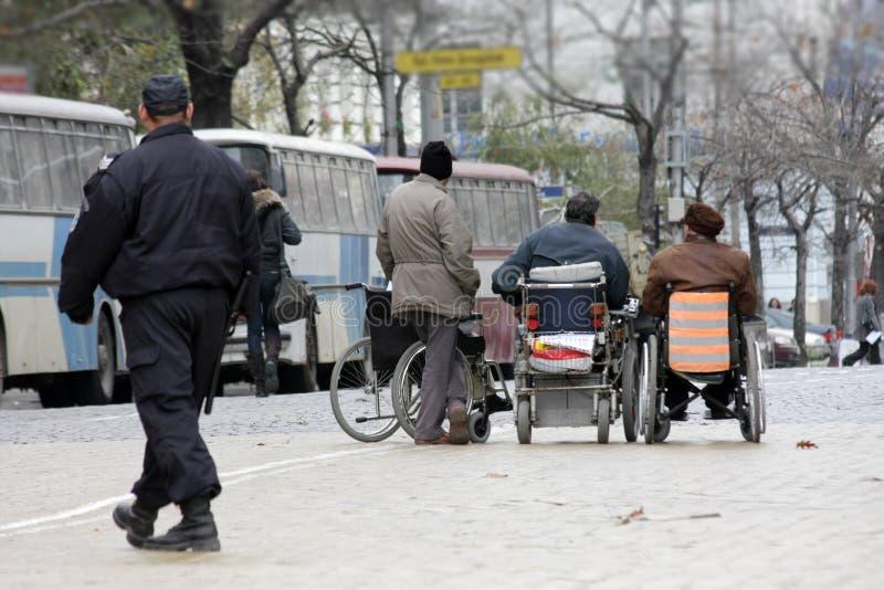 Gente handicappata in sedie a rotelle su una via Persona invalida La gente dello svantaggio fotografia stock