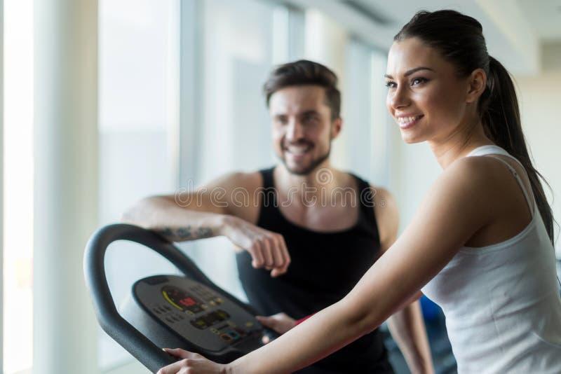 Gente hermosa, joven que habla en un gimnasio mientras que se resuelve fotografía de archivo