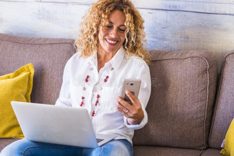 Gente independiente en el trabajo en casa - mujer caucásica adulta hermosa sentarse en el sofá con el funcionamiento del disposit fotos de archivo