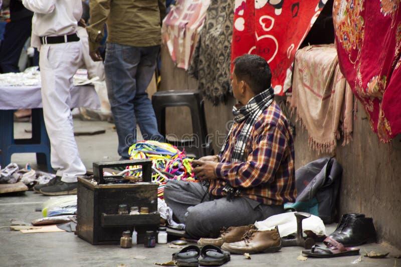 Gente india que trabaja y esperar los zapatos de cuero de pulido del hombre de negocios extranjero en Janpath y el bazar tibetano imagenes de archivo