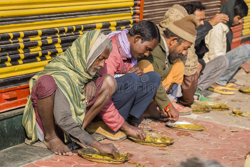 Gente indiana povera che mangia alimento libero alla via a Varanasi, India immagini stock libere da diritti