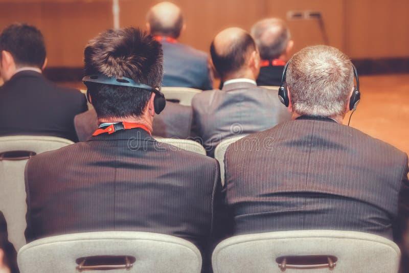 Gente irreconocible de la conferencia que usa los auriculares para la traducción durante acontecimiento los hombres escuchan la t imagenes de archivo
