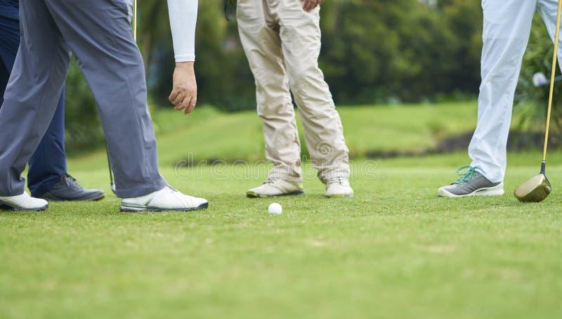 Gente irreconocible que juega a golf en curso, la situación y hablar imágenes de archivo libres de regalías