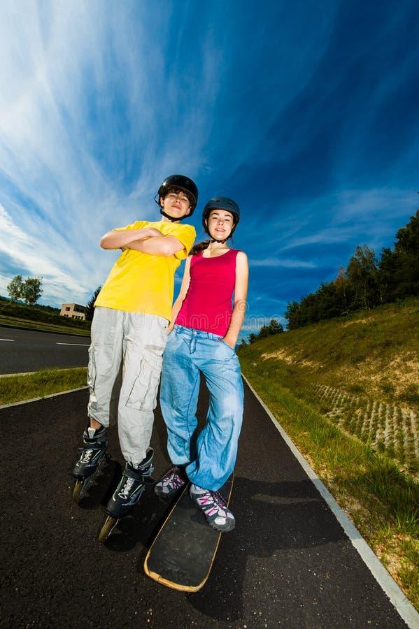 Gente joven activa - el rollerblading, andando en monopatín imagenes de archivo