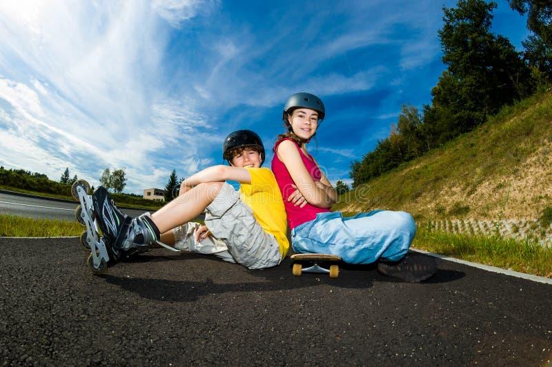 Gente joven activa - el rollerblading, andando en monopatín fotografía de archivo