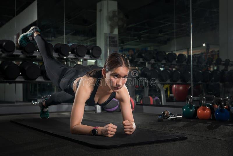 Gente joven apta que hace flexiones de brazos en un gimnasio que mira morenita enfocada, magnífica que calienta y que hace alguno imágenes de archivo libres de regalías