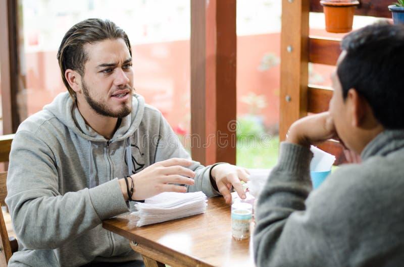 Gente joven apuesta que fija la tabla con las servilletas foto de archivo