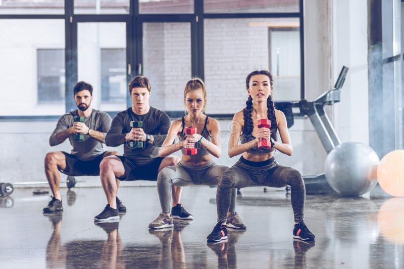 Gente joven atlética en ropa de deportes con pesas de gimnasia que ejercita en el gimnasio fotografía de archivo
