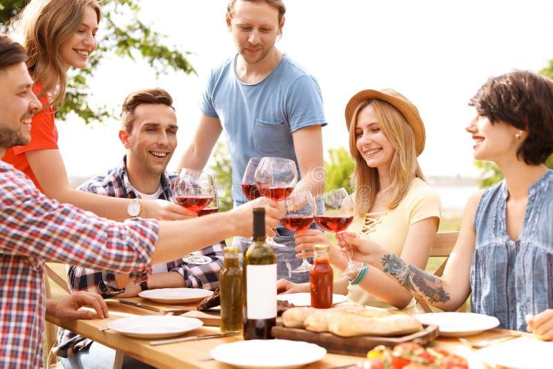 Gente joven con el vino en la tabla al aire libre Barbacoa del verano imágenes de archivo libres de regalías
