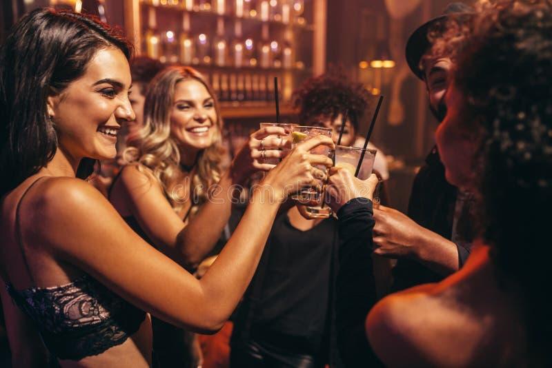 Gente joven con los cócteles en el club nocturno fotografía de archivo