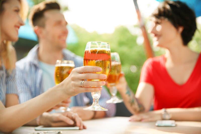 Gente joven con los vidrios de cerveza fría fotografía de archivo libre de regalías