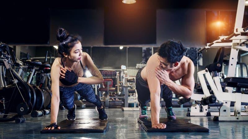 Gente joven de la aptitud que hace flexiones de brazos en un gimnasio que mira la cara e feliz imágenes de archivo libres de regalías