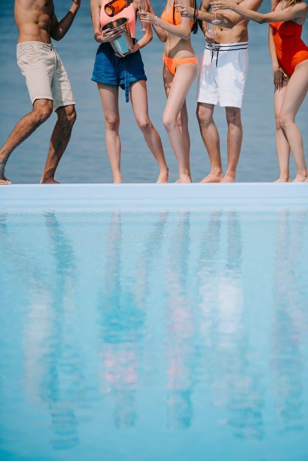 gente joven joven de la sección baja que coloca la piscina cercana y que bebe el champán fotografía de archivo